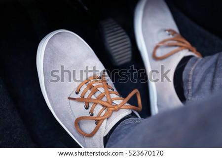 Human feet pressing car pedal