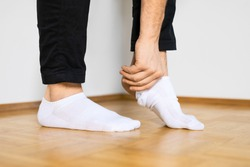 human feet putting on white ankle socks by hand standing on wooden floor
