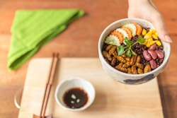 Human female hands holding insects food with Rice Berry in a retro bowl. Healthy meal high protein diet concept. Close-up, Selective focus.