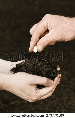 Human fertility concept. Male hands sowing female hand with soil