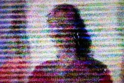 Human figure on television screen with static noise caused by bad signal reception