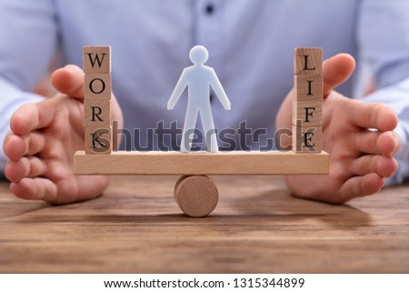 Human Figure Standing Between Work And Life Wooden Blocks On Seesaw Being Protected By Businessperson