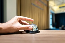 Human finger is press to ringing the bell as a time keeper in meeting presentation or calling the hotel service, concept action. Close-up and selective focus photo.