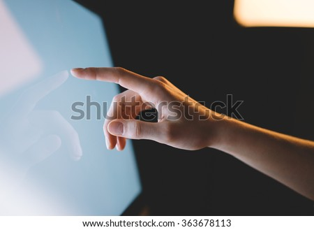 Human finger pointing on the glowing computer screen with blue and blur effects flare side view close-up