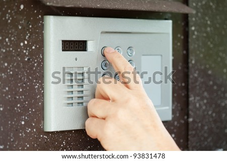 Human finger pushing button of house intercom - stock photo