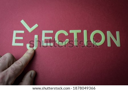 Photo of  Human fingers sliding a letter to the word Election to make it Ejection, written with plastic letters on a dark red paper background, concept