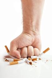 Human fist breaking cigarettes Anti smoking concept