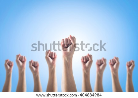 Human fist gesture among blur arm group on blue sky background: Female woman clenched hand raising up showing power strong bunch of five: Women rights strengthening empowering conceptual idea: May day