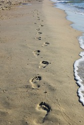 Human footprints on a sandy sea beach stretching into the distance. To the right the waves roll onto the shore