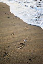 Human footprints on sand of the tropical beach and white sea wave. Sea waves run over the sandy shore.