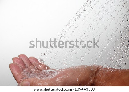 Human hand and falling water.