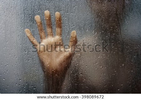Stock Photo human hand and unrecognizable silhouette behind wet glass in shower