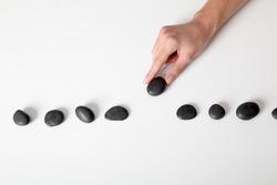 Human hand arranging line of pebbles