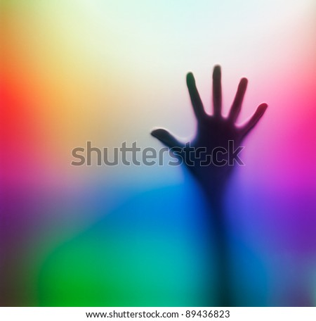 Human hand behind glass. Colorful abstract background.