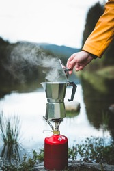 Human hand brewing geyser coffee maker while preparing boiling tea or coffee on camping gas stove by the lake. Camping cooking in nature outdoor. Tourism recreation outside and campsite lifestyle.
