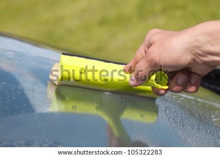 Human hand cleaning window.