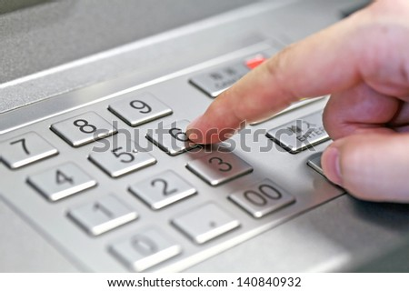 Human hand enter atm banking cash machine pin code