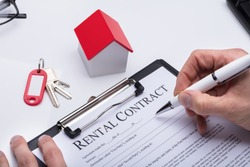 Human Hand Filling Rental Contract Form With House Model And Key On Desk