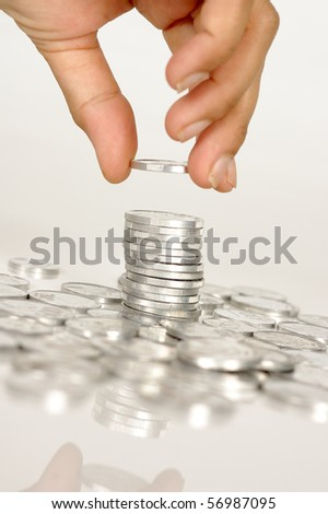 Human hand hold a coin on pile of coins