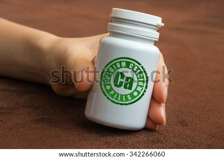 Human hand holding a bottle of pills with calcium on brown background