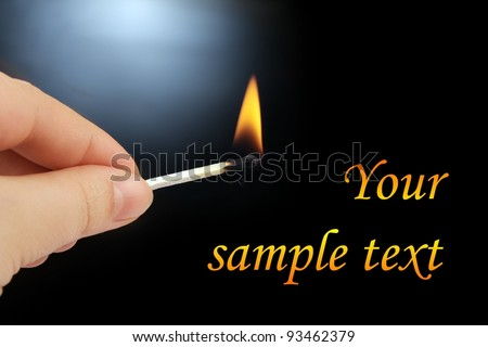 Human hand holding a burning match on a black background