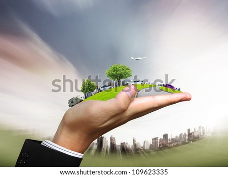 human hand holding a city and nature