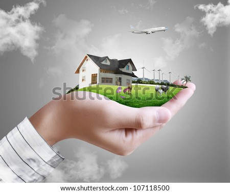 human hand holding a house ands nature