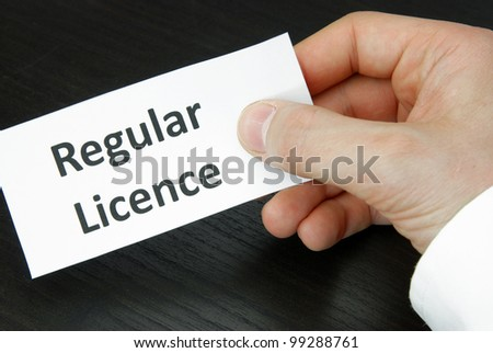 Human Hand holding a Regular Licence Sign