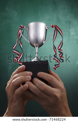 Human hand holding a silver trophy.