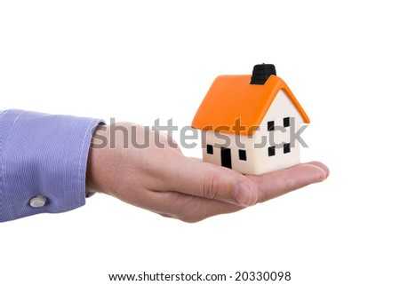 human hand holding a small house