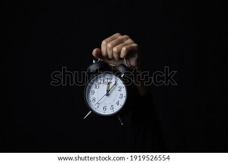 Human hand holding alarm clock in the dark, Copy space. ストックフォト ©