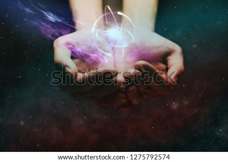 Human hand holding atom on a palm. Nebula dust in infinite space. Mixed media.