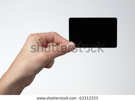 Human hand holding credit card by the corner