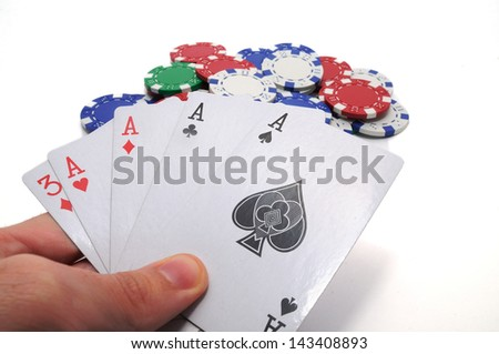 Human hand holding four aces, including spades, hearts, clubs and diamonds, and a bunch of poker chips isolated on white background.