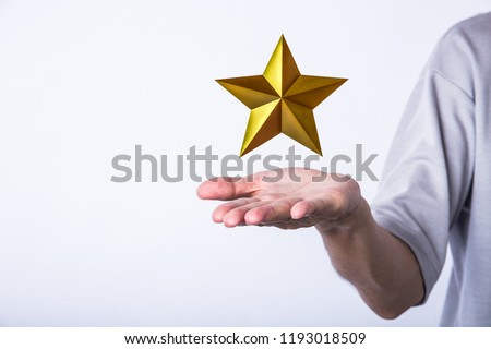 human hand holding golden star