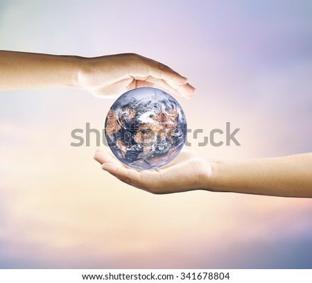 Human hand holding medium green plant with soil on blurred abstract. Ecology, World Environment, Tree of Knowledge concept.Elements of image (like cloud map, world map, etc) are furnished by NASA
