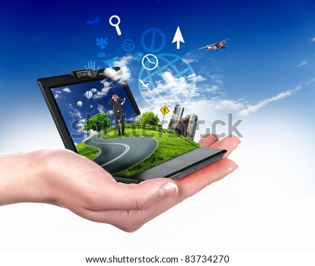 human hand holding notebook and nature landscape in it - stock photo