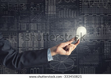 Human hand holding shining electric bulb and infographs on wall #333450821