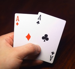 human hand holding two aces on black wood table
