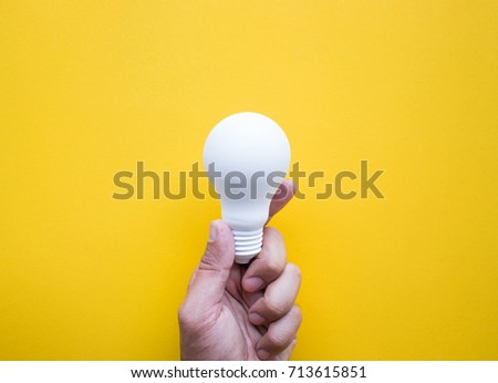 Human hand holding white lightbulb on pastel color background.Ideas creativity,inspiration,concepts.Flat lay design.