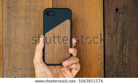 Human hand holding wood texture smartphone case.