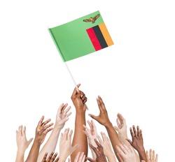 Human hand holding Zanbia Flag among multi-ethnic group of people's hand