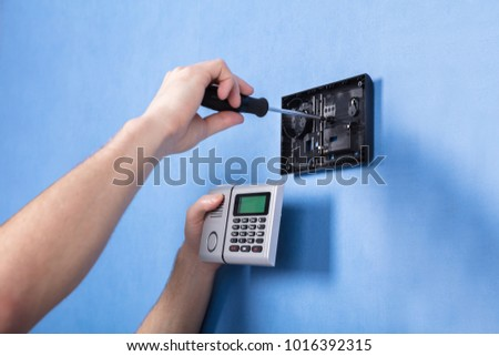 Human Hand Installing Security System On Blue Wall #1016392315