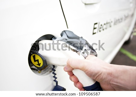 Human hand is holding Electric Car Charging nozzle. Selective focus on hand and nozzle
