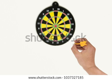 Human hand is throwing the darts target to the darts board