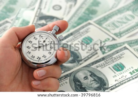 Human hand keeping a stop-watch against dollar bank note
