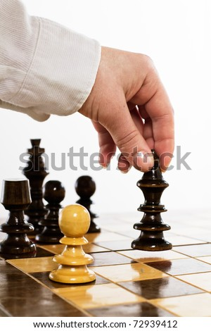 Human hand move black king on chessboard.
