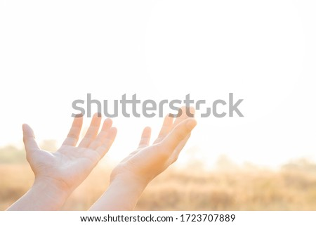 Human hand open palm up worship praying with faith and belief in God of an appeal to the sky and sunlight outdoor. Concept religion and spirituality with believe Power of hope or love and devotion.