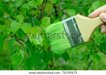 Human hand painting green leaves with green color paint