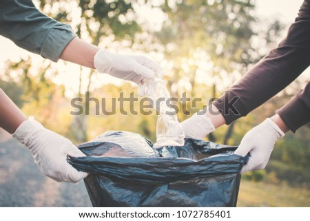 Human hand picking up plastic into bin bag on park ,volunteer concept #1072785401